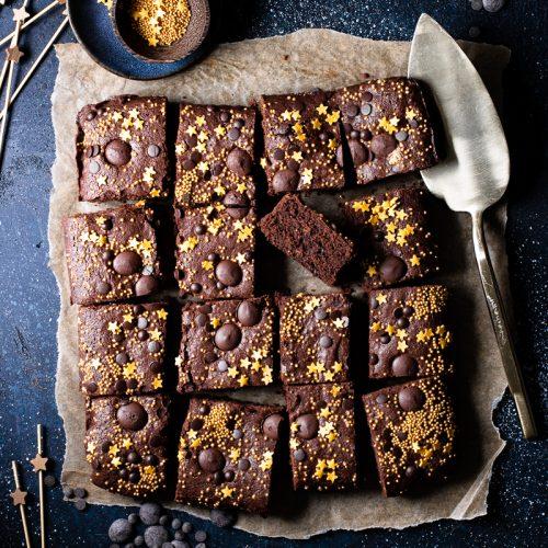quadrati di brownie senza glutine e senza lattosio con stelline dorate come decorazione su sfondo blu scuro