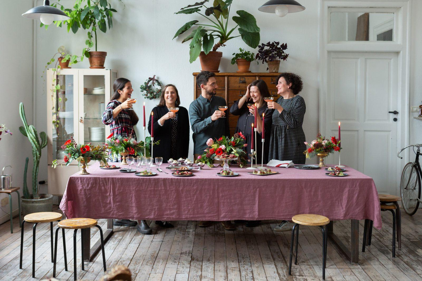 cinque persone che brindano davanti a un tavolo imbandito