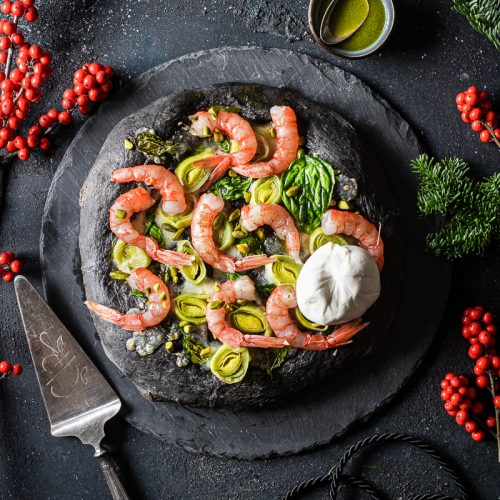 Piatto di ardesia con focaccia al nero di seppia, gamberi rossi e burrata
