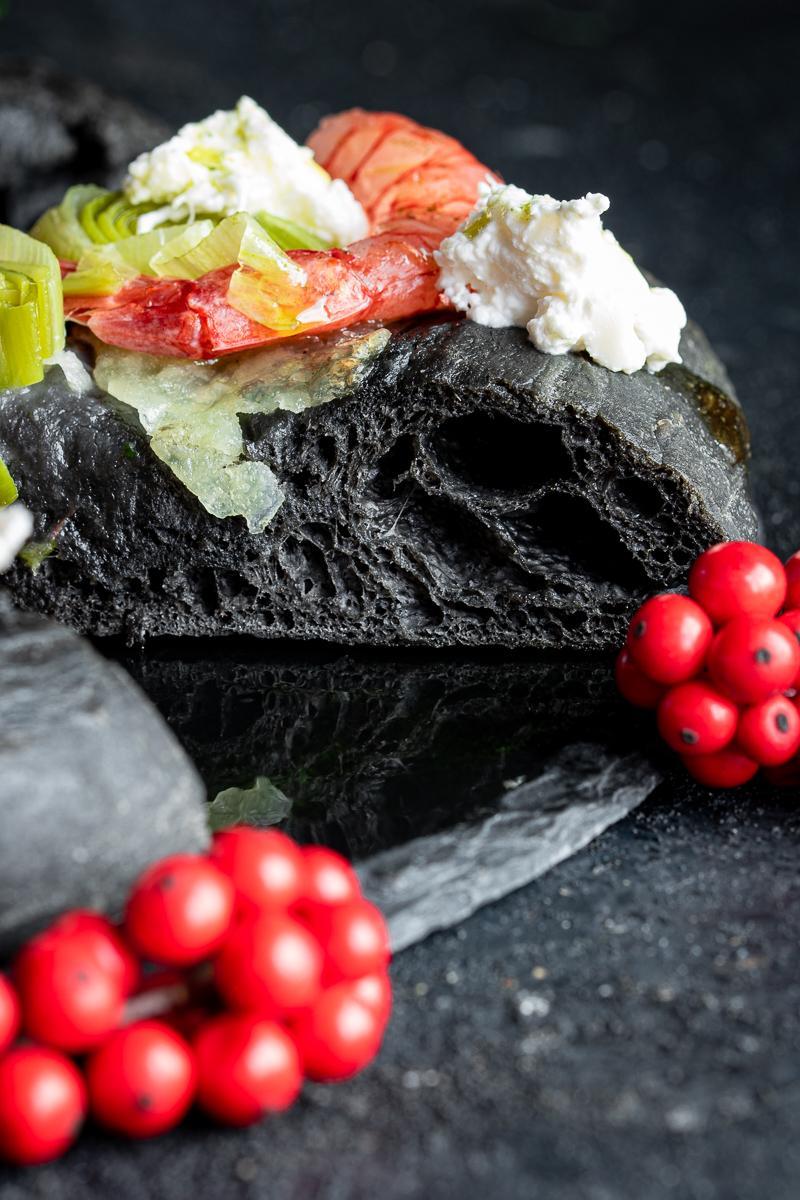 alveolatura di una fetta di focaccia al nero di seppia con gamberi rossi e porri