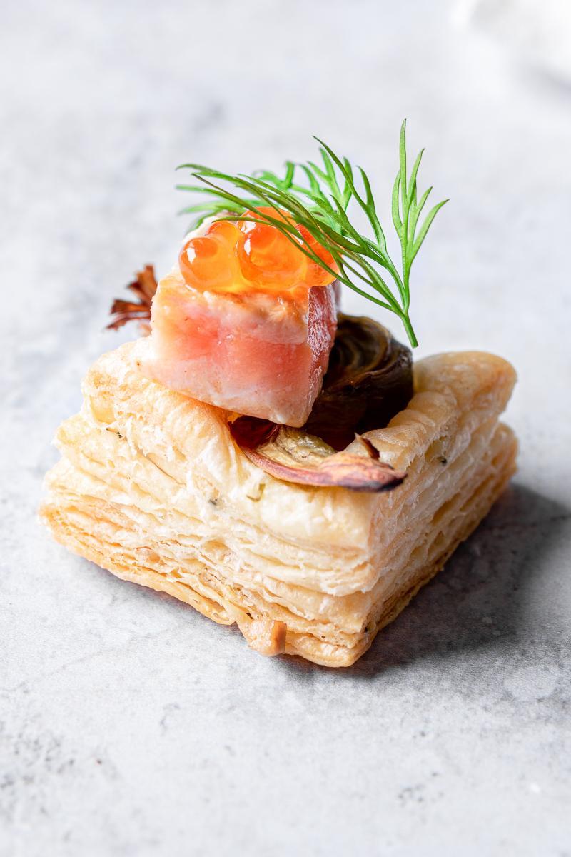 Foto ravvicinata di un salatino di sfoglia furba con salmone, carciofo, roe e aneto