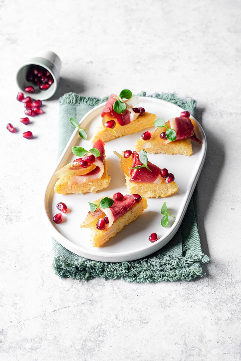 Vassoio ovale moderno con triangolini di polenta con speck d'anatra, mostarda di fichi, melograno e fermogli