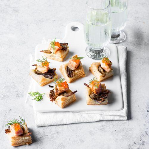 Salatini di sfoglia con salmone e carciofi su un vassoio di ceramica bianca con tovagliolo e due bicchieri