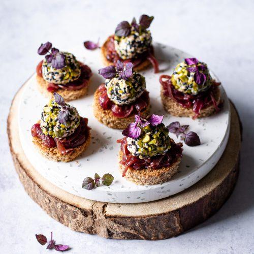 Vassoio di legno e di marmo sovrapposti con tartine di pane di farro con palline di formaggio di capra e cipolle caramallate