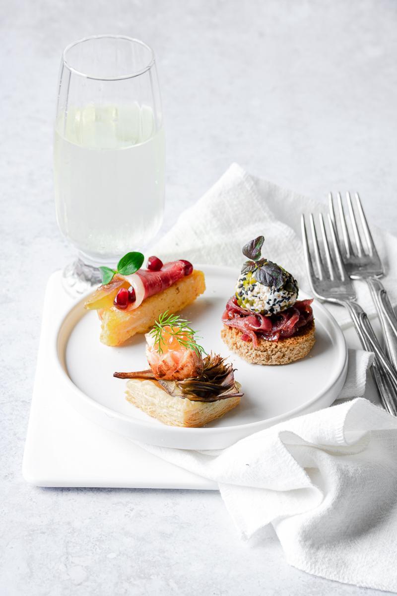 3 stuzzichini per capodanno su un piatto bianco con un bicchiere di spumante