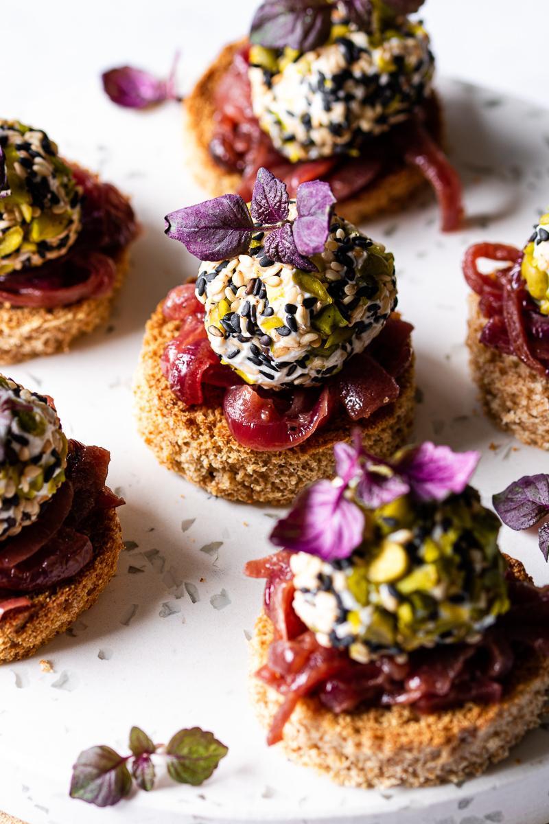 Foto macro di tartine di pane di farro con palline di caprino e semi e cipolle caramellate