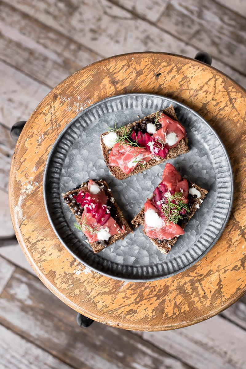 Piatto zincato con tre tartine di pane nero con carpaccio, lenticchie e barbabietola, su uno sgabello di legno