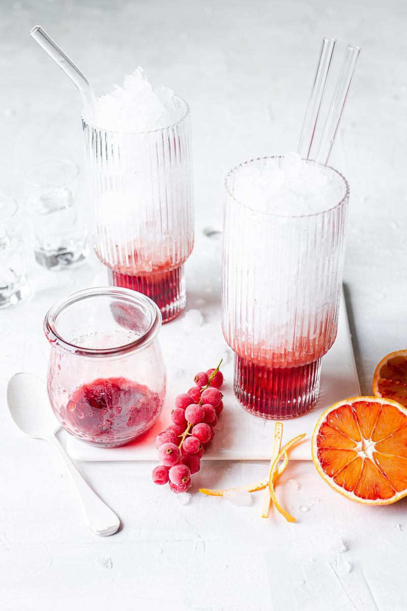 Bicchieri pieni di ghiaccio tritato e fondo con sciroppo di melograno e arancia rossa, vasetto sporco e frutta sparsa