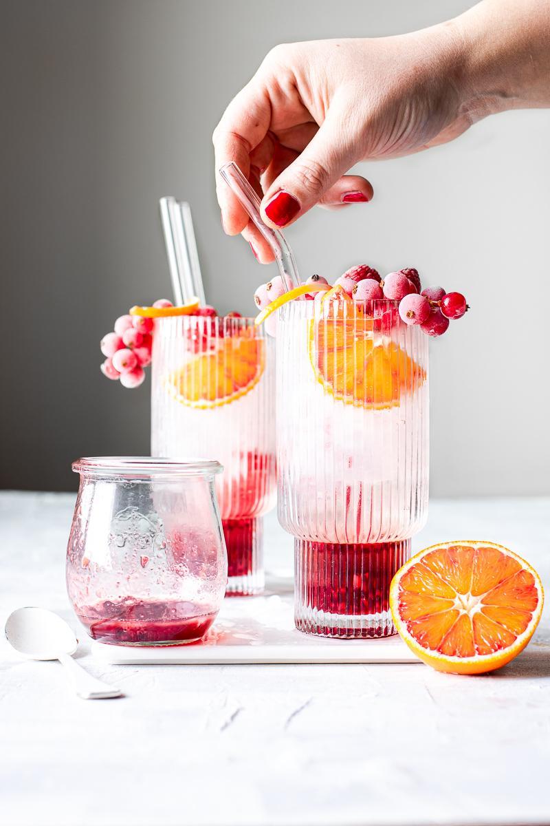 Mano che prende una cannuccia di vetro immersa in un bicchiere di kir gin tonic con frutti di bosco congelati