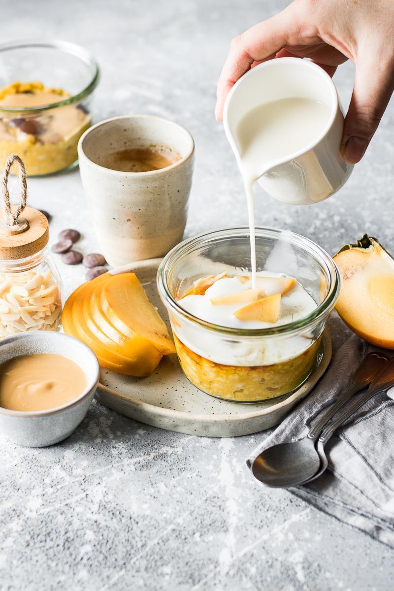 Bricco che versa latte vegetale sopra un porridge alla zucca in vasocottura