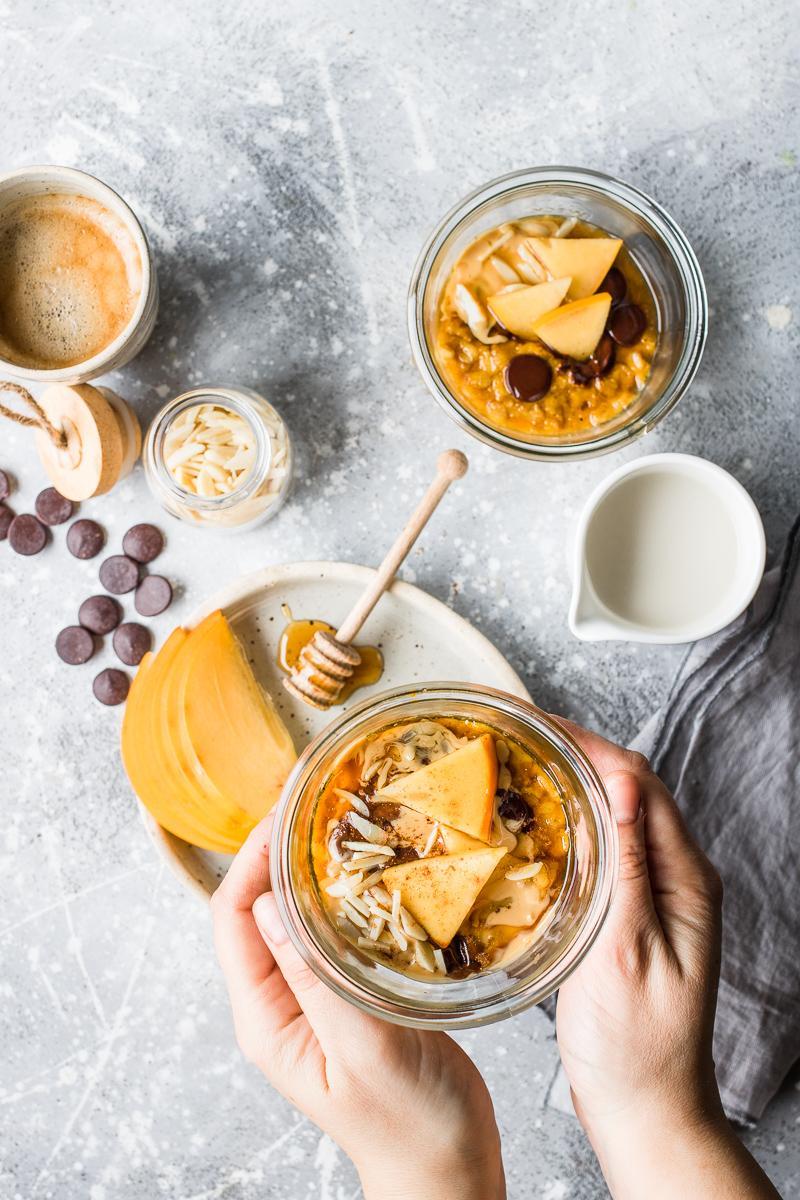 Tavola per la colazione con porridge alla zucca in vasocottura vegano cioccolato e cachi mela