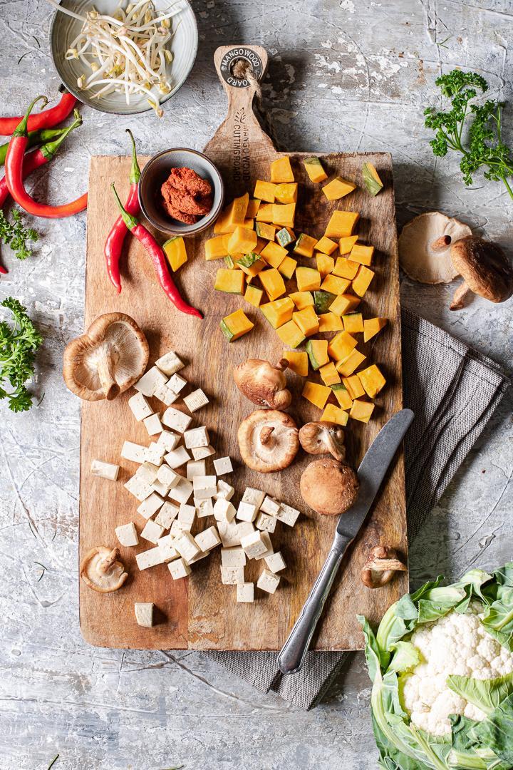 tagliere di legno con zucca, funghi, cubetti di tofu e peperoncino