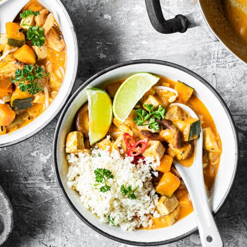 ciotola di red curry vegano low carb con riso di cavolfiore e fettine di lime