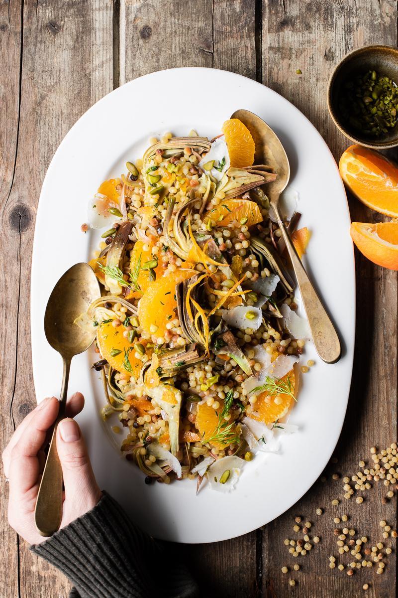 Vassoio bianco con insalata di fregola con carciofi, arancia, bottarga, pecorino e pistacchi