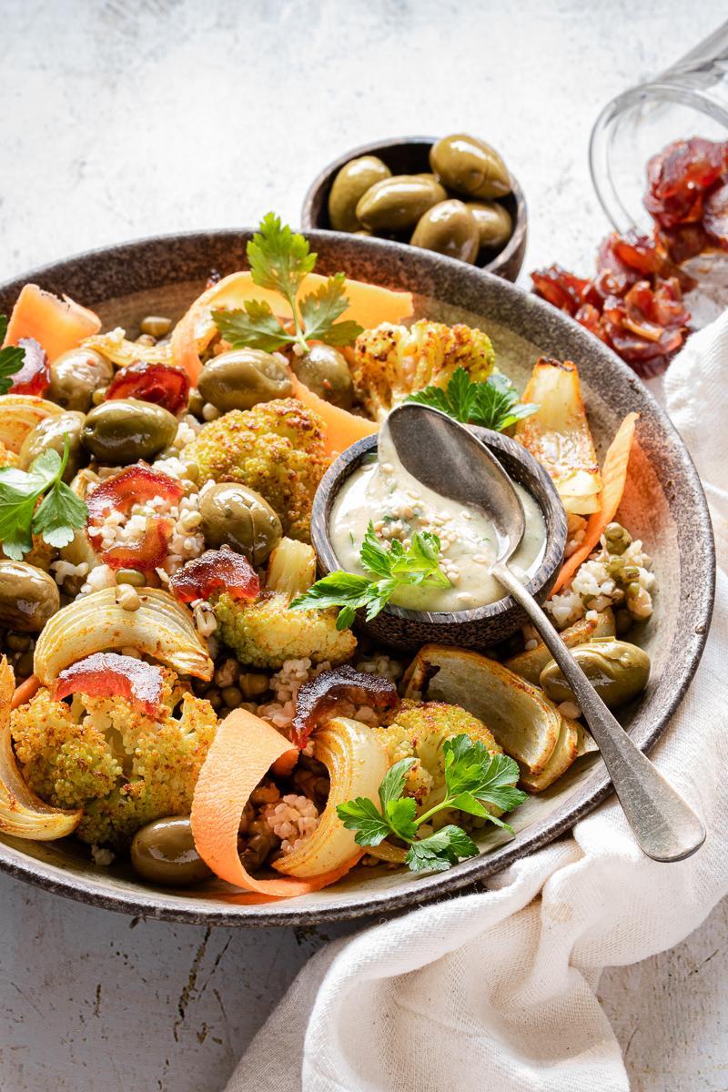 Insalata di cavolfiore arrosto con bulgur, fagioli, datteri e carote in una ciotola