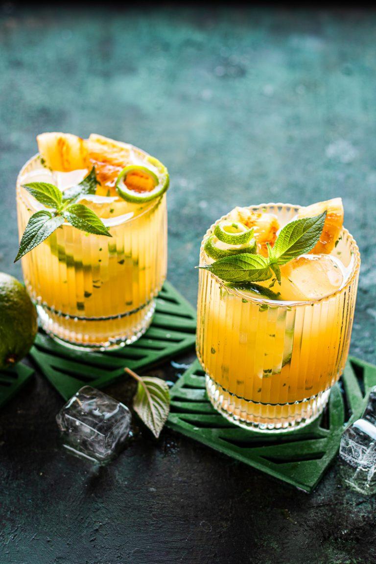 due bicchieri contenti un cocktail all'ananas tipo paloma