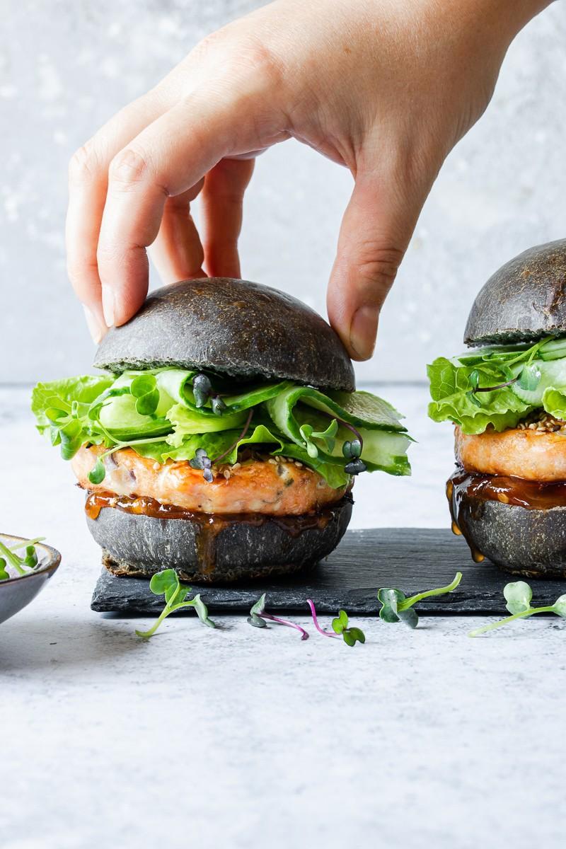 Hamburger di salmone con bun al nero di seppia, cetrioli e salsa senapata
