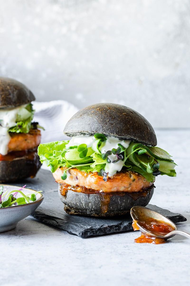 Hamburger di salmone con bun al nero di seppia, cetrioli e salsa allo yogurt