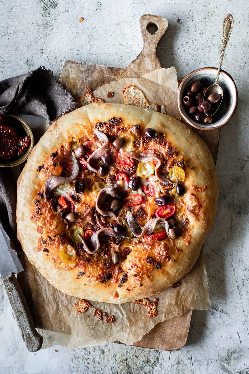 pizza con acciughe pesto di pomodorini e olive