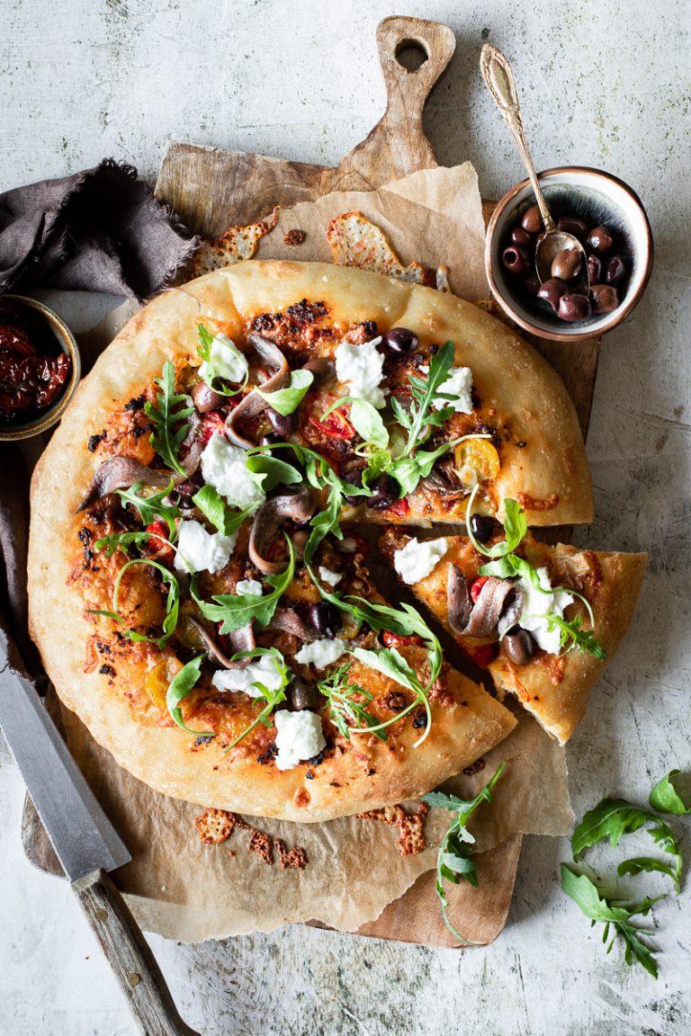 pizza con acciughe pesto di pomodorini rucola e burrata