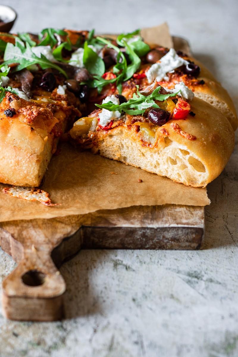 pizza alta con acciughe pesto di pomodorini rucola e burrata