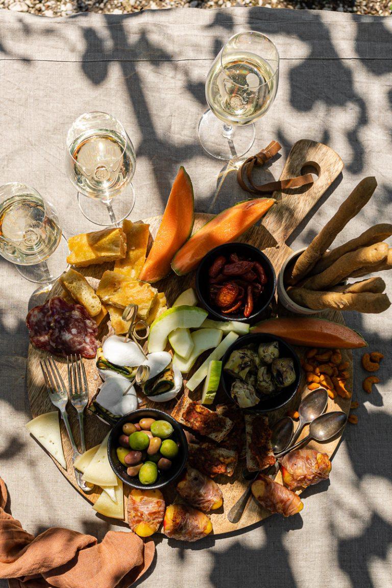 tagliere da aperitivo estivo pieno di cibo su tovaglia rustica con bicchieri di vino e ombre di viti